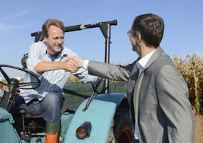 Germany, Bavaria, Farmer welcomes businessman with handshake while sitting on a tractor in cornfield